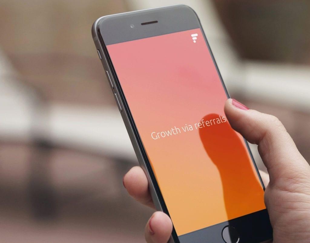 Smartphone mit Firal Logo und Claim growth via referrals