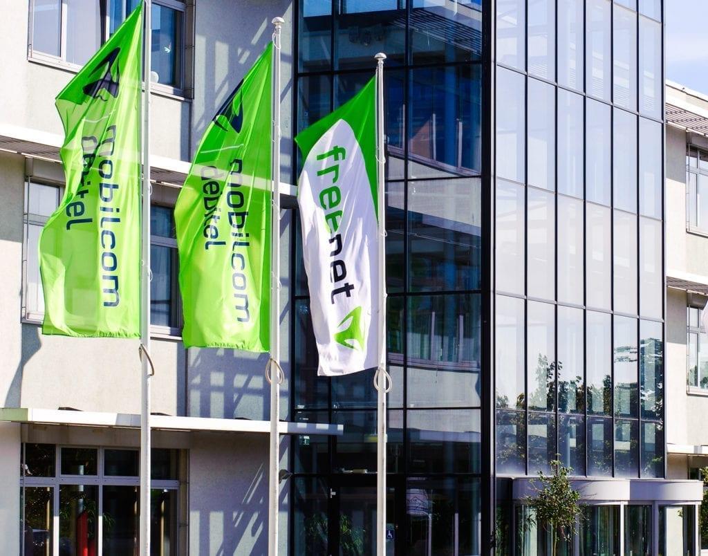 Freenet und mobilcom debitel Logos auf Fahnen vor Geschäftsgebäude