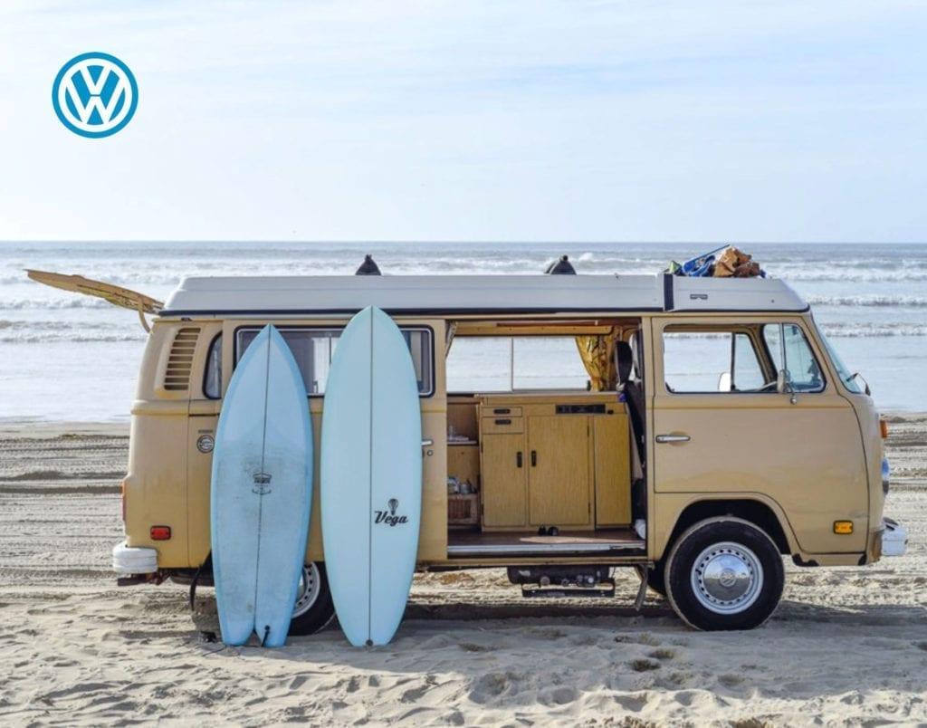 VW Bus und Surfbretter am Strand