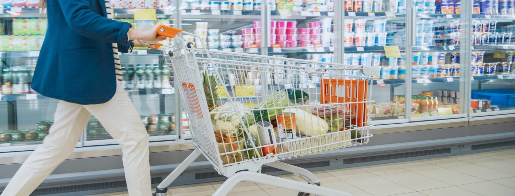 Einkaufswagen vor dem Kühlregal im Supermarkt