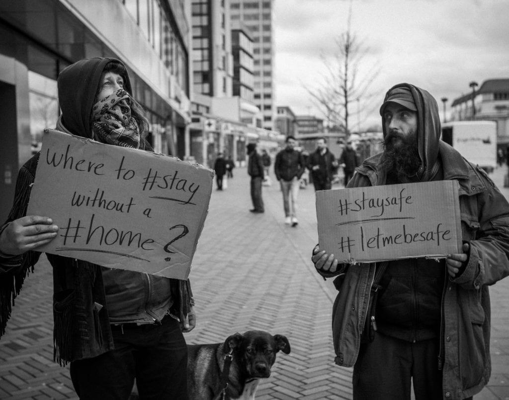 Schwarz-weiß Foto. Zwei Obdachlose mit Hund, die Schilder tragen. Schild 1: Where to #stay without a #home ? Schild 2: #staysafe #letmebesafe