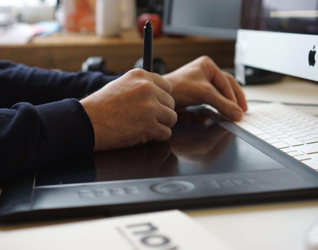 Bild im Text: Nahaufnahme der Hände unseres Reinzeichners Marc Lehmann bei der Arbeit am Grafik Board.