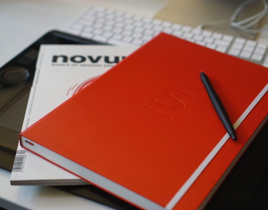 Bild im Text: DinA4 Notizbuch in rotem Syndicate Branding auf einer Zeitschrift und einem Grafik Board.