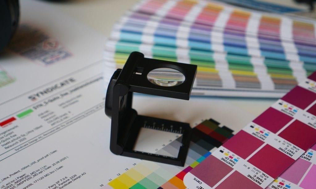 Header: Eine Lupe, Farbpaletten und der Druck einer Reinzeichnung.